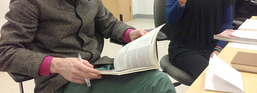 cropped photo of a person sitting with an open book in their lap and a pen in their right hand